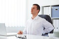 El hombre de negocios joven tiene dolor de espalda Imagen de archivo