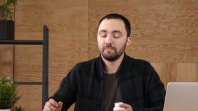 El hombre de negocios joven toma la medicina mientras que se sienta en el lugar de trabajo delante del ordenador portátil almacen de metraje de vídeo