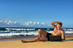 El hombre de negocios joven trabaja con el cuaderno en la playa Fotos de archivo libres de regalías