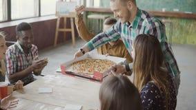 El hombre de negocios joven trae la pizza al equipo de la raza mixta en la oficina moderna El grupo de personas feliz está aplaud almacen de video