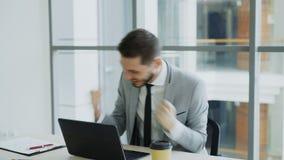 El hombre de negocios joven usando el ordenador portátil que recibe el buen mensaje y llegado a ser muy emocionado y feliz se sie