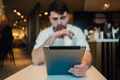 El hombre de negocios joven utiliza un Tablet PC en un restaurante acogedor antes de su orden Fotografía de archivo libre de regalías