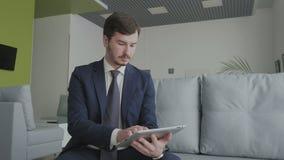 El hombre de negocios joven utiliza una tableta en un pasillo del salón del vip en el aeropuerto metrajes