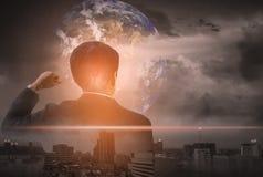 El hombre de negocios de la exposición doble, se levanta, aumenta su mano, ciudad y mundo del paisaje del fondo, visión del conce fotografía de archivo libre de regalías