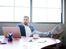 El hombre de negocios lanzó sus piernas en el escritorio para relajarse imagen de archivo libre de regalías