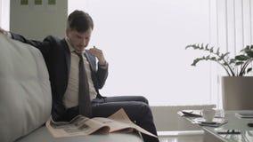El hombre de negocios lee un periódico en pasillo del salón del vip en el aeropuerto metrajes