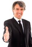 El hombre de negocios lleva a cabo hacia fuera su mano Fotografía de archivo libre de regalías