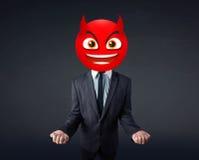 El hombre de negocios lleva la cara del smiley del diablo Fotografía de archivo libre de regalías
