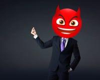 El hombre de negocios lleva la cara del smiley del diablo Fotos de archivo