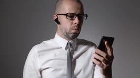 El hombre de negocios lleva una conversación seria con un colega en el teléfono almacen de metraje de vídeo