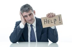 El hombre de negocios maduro desamparado que celebra una ayuda firma en la tensión del desempleo de la crisis financiera y el con fotos de archivo libres de regalías