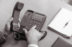 El hombre de negocios marca el número en el teléfono de la línea horizonte Fotos de archivo libres de regalías