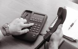 El hombre de negocios marca el número en el teléfono de la línea horizonte, sostiene el microteléfono en su mano derecha Imagen de archivo