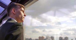 El hombre de negocios masculino acertado serio se está colocando en la oficina cerca de la ventana y está disfrutando del panoram almacen de video
