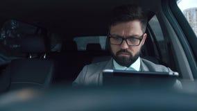 El hombre de negocios masculino atractivo con una barba aseada mira la tableta almacen de video