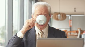 El hombre de negocios mayor bebe la bebida caliente en el café