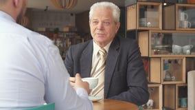 El hombre de negocios mayor escucha su socio