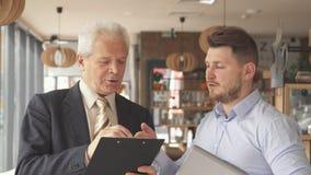 El hombre de negocios mayor explica algo en el tablero a su socio almacen de video