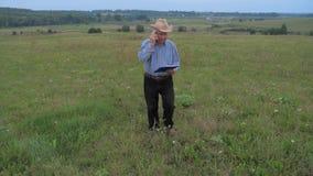 El hombre de negocios mayor Goes On del granjero el campo, habla en el teléfono metrajes