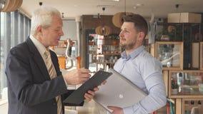 El hombre de negocios mayor hace algunas preguntas a su socio más joven