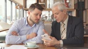 El hombre de negocios mayor muestra a su socio algo en su smartphone