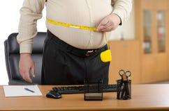 El hombre de negocios mide su cintura por el metro de la cinta en el escritorio Imagen de archivo