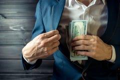 El hombre de negocios, el miembro o el oficial pone un soborno en su bolsillo Imágenes de archivo libres de regalías