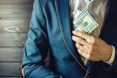 El hombre de negocios, el miembro o el oficial pone un soborno en su bolsillo Imagenes de archivo
