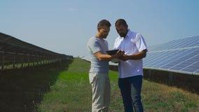 El hombre de negocios mira documentos en las baterías solares almacen de video