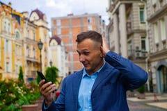 El hombre de negocios mira en teléfono pruebas un choque y una sorpresa imagenes de archivo