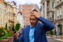 El hombre de negocios mira en teléfono pruebas un choque y una sorpresa imagen de archivo libre de regalías