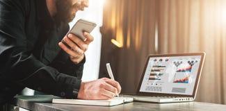 El hombre de negocios mira la pantalla del ordenador portátil, haciendo una nota en cuaderno mientras que sostiene smartphone El  imagen de archivo libre de regalías