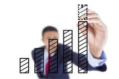 El hombre de negocios mira para arriba y crecimiento de la barra del gráfico de la escritura Fotos de archivo