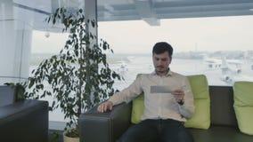 El hombre de negocios mira su documento de embarque en el aeropuerto almacen de video