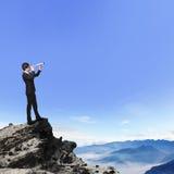 El hombre de negocios mira a través del telescopio en la montaña Imagen de archivo libre de regalías