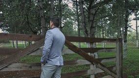 El hombre de negocios mira una granja almacen de metraje de vídeo