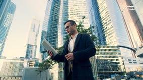 El hombre de negocios mira una tableta, colocándose cerca de rascacielos, vista lateral