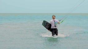 El hombre de negocios monta una cometa en el océano tropical y realiza la cámara lenta de los trucos metrajes
