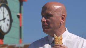 El hombre de negocios muerto de hambre leyó noticias en línea del teléfono móvil y comer un bocado metrajes