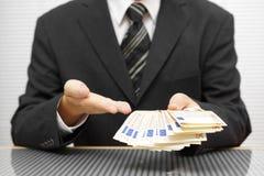El hombre de negocios muestra que usted toma el dinero y acepta el trato finan Imagen de archivo