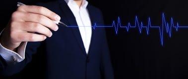 El hombre de negocios muestra un cardiograma foto de archivo