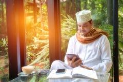 El hombre de negocios musulmán árabe se sienta en cafetería, tableta del uso y elegante Imagenes de archivo