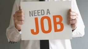 El hombre de negocios necesita un trabajo. Hombre que sostiene la pizarra con NECESIDAD del título UN TRABAJO metrajes