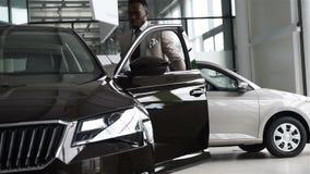 El hombre de negocios negro atractivo joven compra un nuevo coche, sueños viene verdad almacen de metraje de vídeo