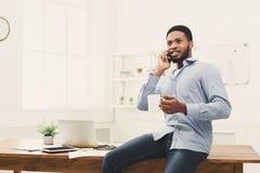El hombre de negocios negro joven tiene charla del teléfono móvil imagen de archivo