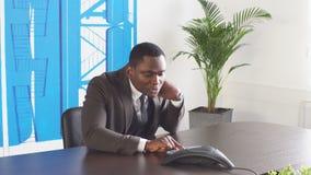 El hombre de negocios negro joven utiliza el teléfono en oficina almacen de video