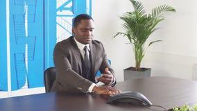 El hombre de negocios negro joven utiliza el teléfono en oficina metrajes