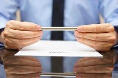 El hombre de negocios o el abogado está analizando el contrato antes de firmar Fotografía de archivo libre de regalías