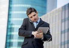El hombre de negocios ocupado que sostenía la tableta digital y el teléfono móvil trabajó demasiado al aire libre Imagenes de archivo