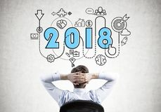 El hombre de negocios de pensamiento que mira 2018 comienza para arriba el icono Imagen de archivo